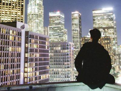man looking at lit up buildings